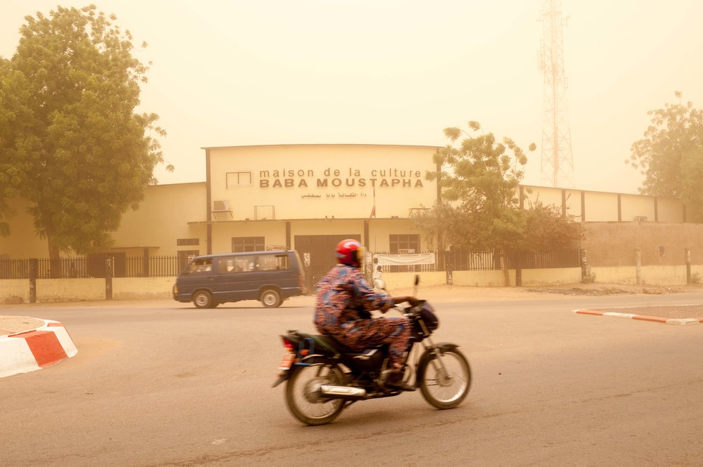 "A man rides a scooter in front of the ""maison de la culture - Baba Moustapha"" during  a sand storm in April 2015, N'Djamena, Chad."