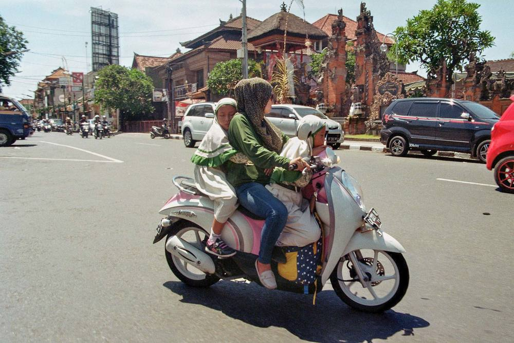 A woman picks up her children after school in Ubud, Bali, Indonesia, 24 February 2016. Scooters are the most popular vehicle on Bali. Local people transport everything on them on the heavy traffic roads of Bali.