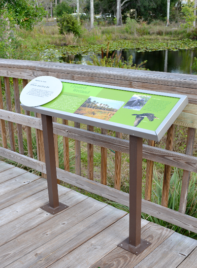 Interpretive signs and donor recognition are combined in the natural environment, highlighting the role of the philanthropy.