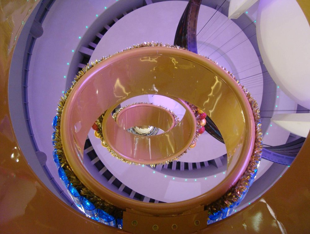 Welded steel, Mylar, mirror, and plastic. 18' x 8' steel frame with hand applied decorative plastic elements and mylar details. Designed for the opening of Dubai's first/primary catwalk for top fashion shows. Sections of the catwalk rise and lower and all surfaces are video screens, an engineering and technical marvel. Our design needed to live with this spectacle and hold its own as a sculptural accent to the space.
