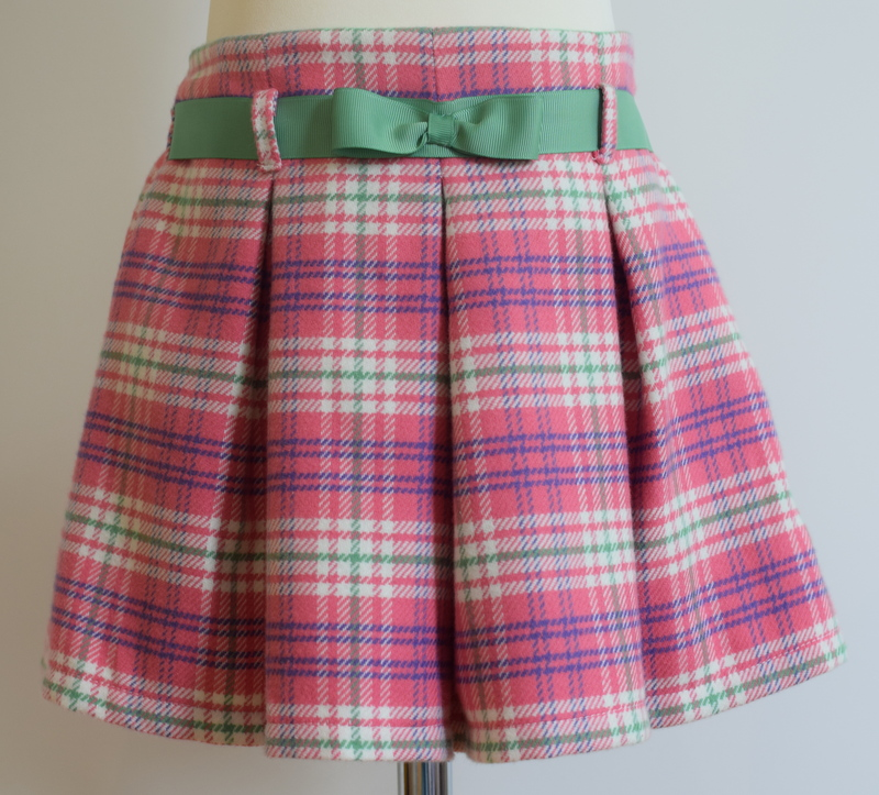 Pink check wool skirt   Description: pretty pleats front and back,contrasting grosgrain ribbon belt, concealed zip at side, adjustable elastic waist  Available in sizes 5y and 9y (SOLD OUT)  From £34