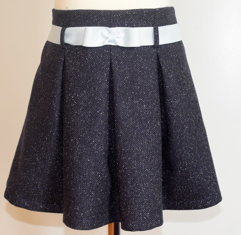 Dark blue speckled wool skirt   Description: pretty pleats front and back,contrasting ice blue grosgrain ribbon belt, concealed zip at side, adjustable elastic waist  Sizes: available in 5y  £34