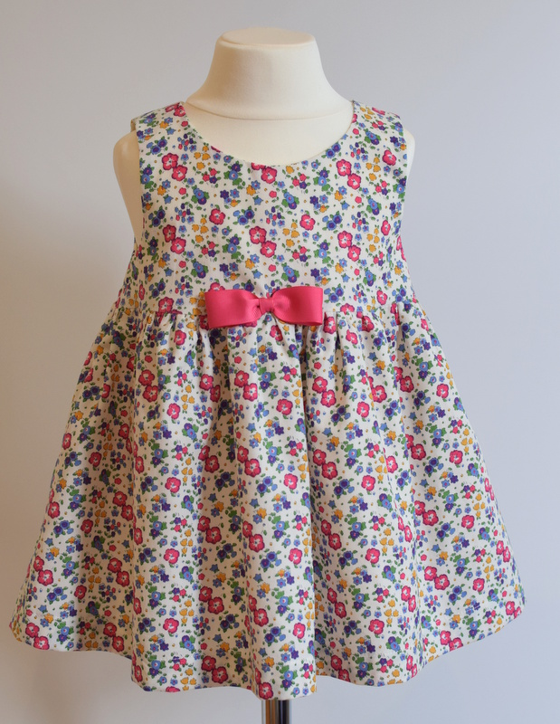 Ella & Libby pink pinafore dress   Description: pretty A-line pinafore style corduroy dress with pleats at the front to give it a lovely fullness, contrasting grosgrain ribbon bow, three buttons at back.Pair with a simple roll neck top or silk blouse.  Sizes: SOLD OUT  Price: £38