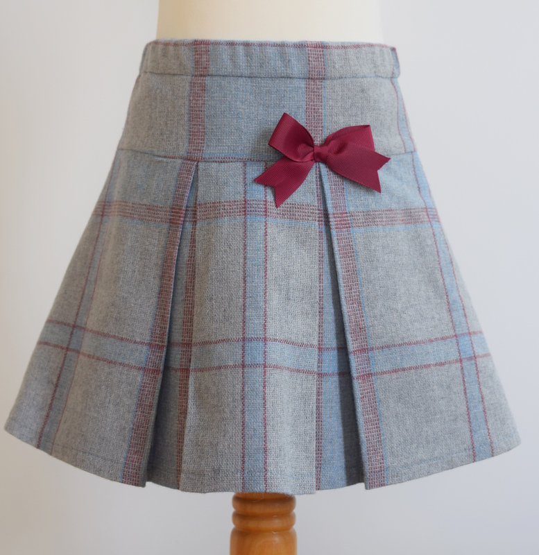 Blue and red check wool skirt   Description: pretty pleats front and back, contrasting grosgrain ribbon bow, concealed zip and button at back, elastic waist  Sizes: available in 3y and 5y  From £32