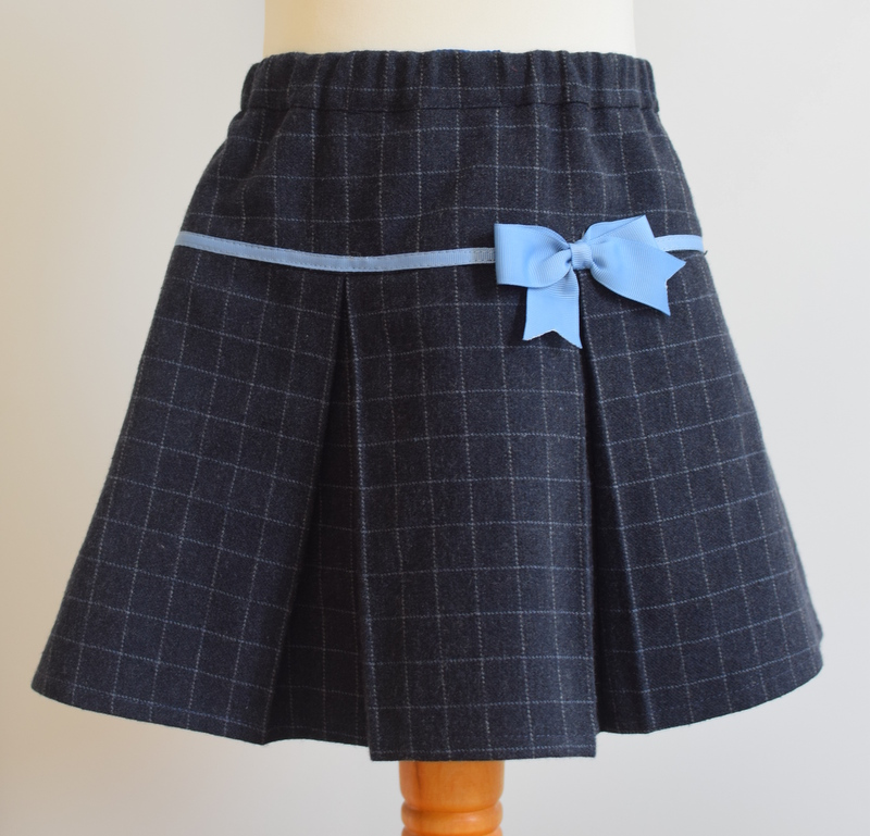 Navy wool skirt   Description: small square check wool with pretty pleats front and back, contrasting grosgrain ribbon bow, concealed zip and button at back, elastic waist  Sizes: SOLD OUT  £34