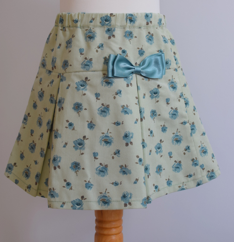 Liberty skirt in soft corduroy   Description: pretty pleats at front,contrasting satin bow, concealed zip and button at back, adjustable elastic waist  Sizes: available exclusively in 6y  £34