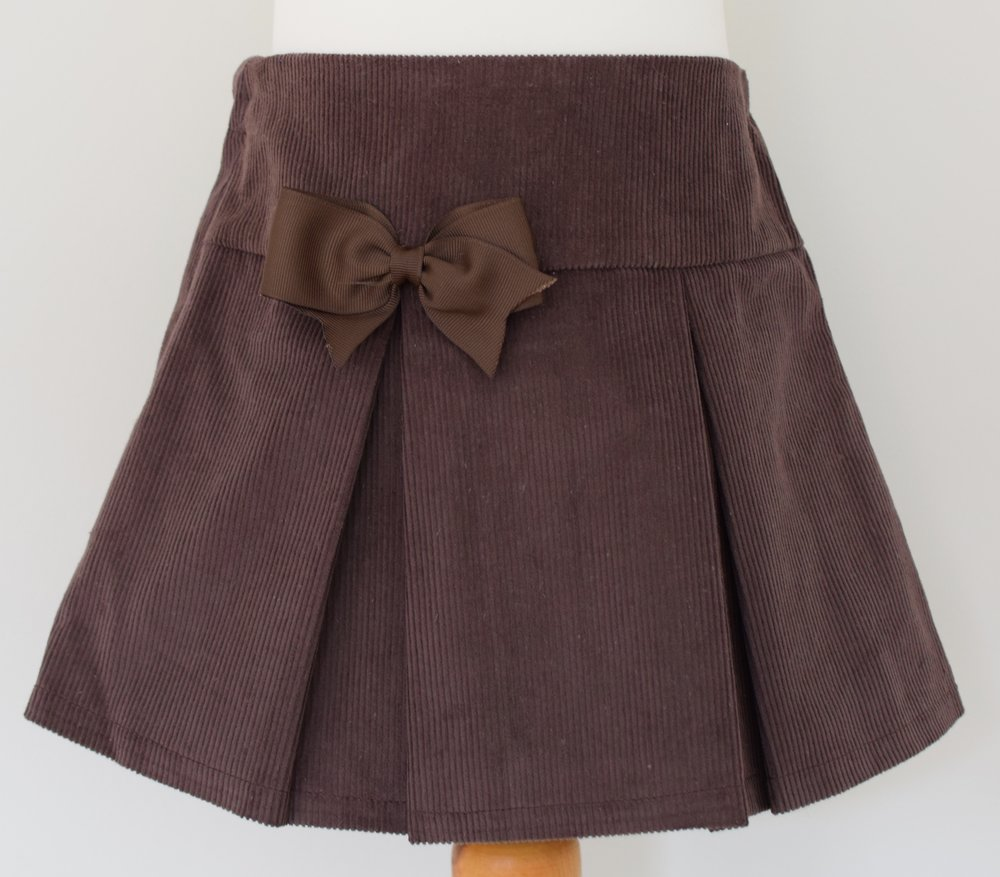 Chocolate corduroy skirt   Description:pretty pleats front and back, contrasting grosgrain ribbon bow, concealed zip and button at back, elastic waist  Sizes: available in 4y, 5y and 6y  £22