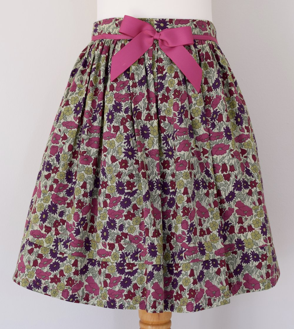 Poppy & Daisy skirt   Description: gathered skirt,contrasting pink grosgrain ribbon bow, concealed zip at back, adjustable elastic waist  Sizes: SOLD OUT  £34