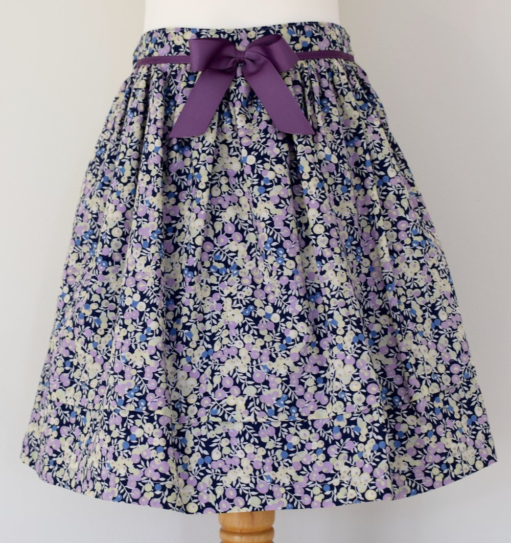 Wiltshire skirt    Description: gathered skirt,contrasting purple  grosgrain ribbon bow, concealed zip at back, adjustable elastic waist   Sizes: available in 6y  £34