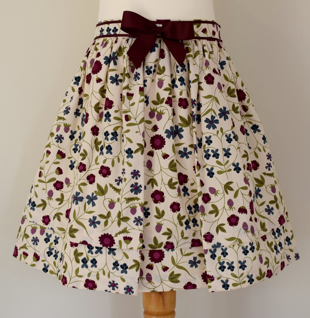 Mirabelle skirt    Description: gathered skirt,contrasting burgundy  grosgrain ribbon bow, concealed zip at back, adjustable elastic waist   Sizes: available in 6y  £34