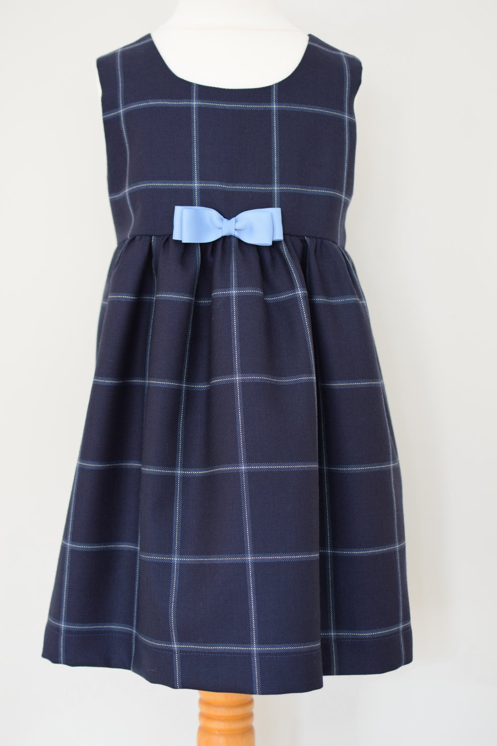 Blue check wool dress   Description: pinafore style dress made from beautifully fine English virgin wool with a gathered skirt and fixed grosgrain bow, concealed zip at back and fully lined.  Sizes: 3y and 5y  Price: from £38