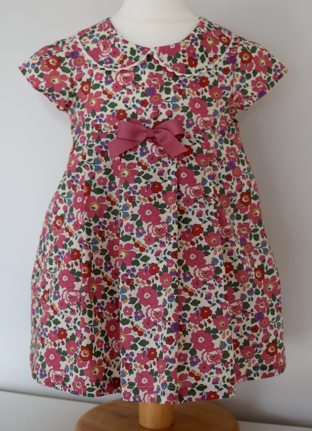 Betsy party dress   A very pretty Liberty print dress with a matching Peter Pan collar trimmed with rick rack ribbon, cap sleeves and a fixed pink grosgrain ribbon. This dress is fully lined with a three button fastening at the back.  Available in sizes 3y, 4y and 5y (SOLD OUT)  From £40
