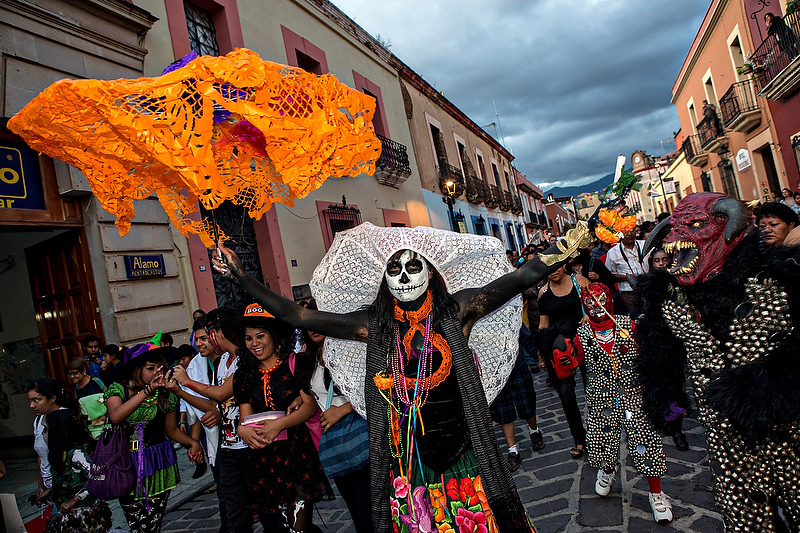 Revelers dance through the streets in traditional costumes at the start of the Day of the Dead festival known in spanish as Día de Muertos October 30, 2013 in Oaxaca, Mexico.