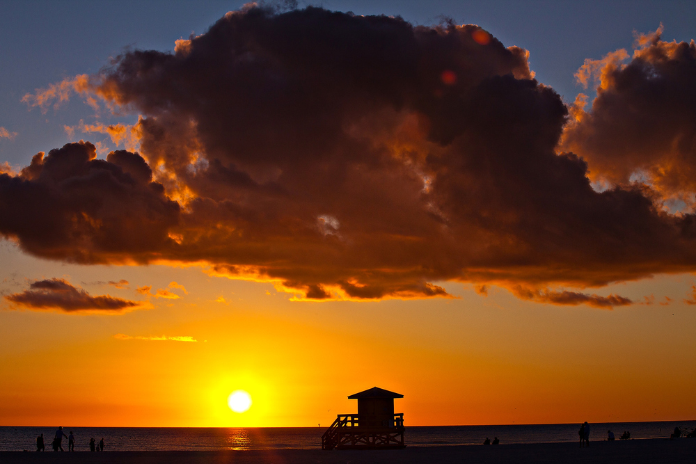Sunset silhouettes lifeguard station on famed white powder sand Siesta Key beach, Sarasota Florida
