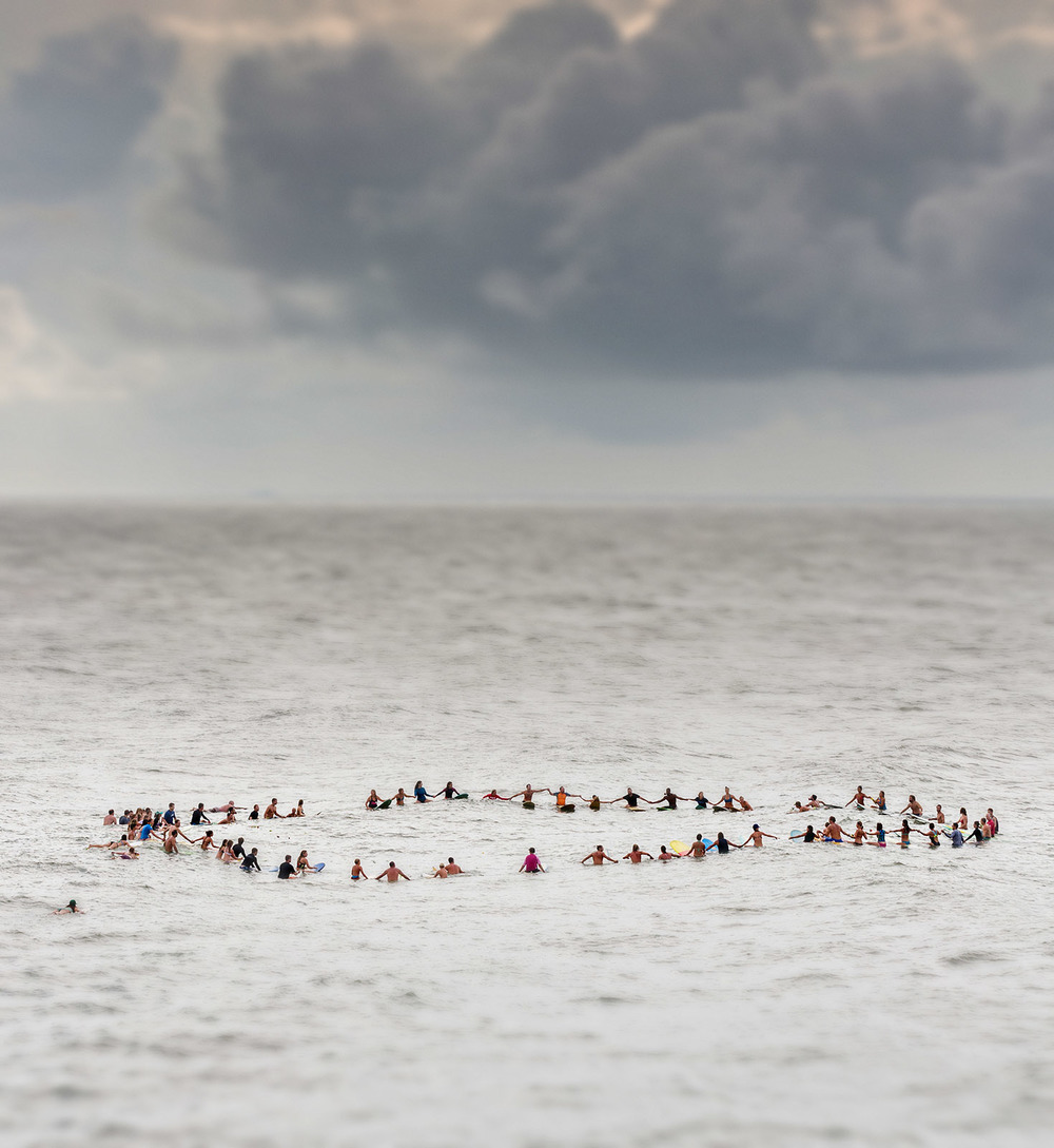 Charleston area surfers join hands in a floating circle during a traditional memorial paddle out to honor and remember the nine people killed at the historic mother Emanuel African Methodist Episcopal Church in Folly Beach, South Carolina.