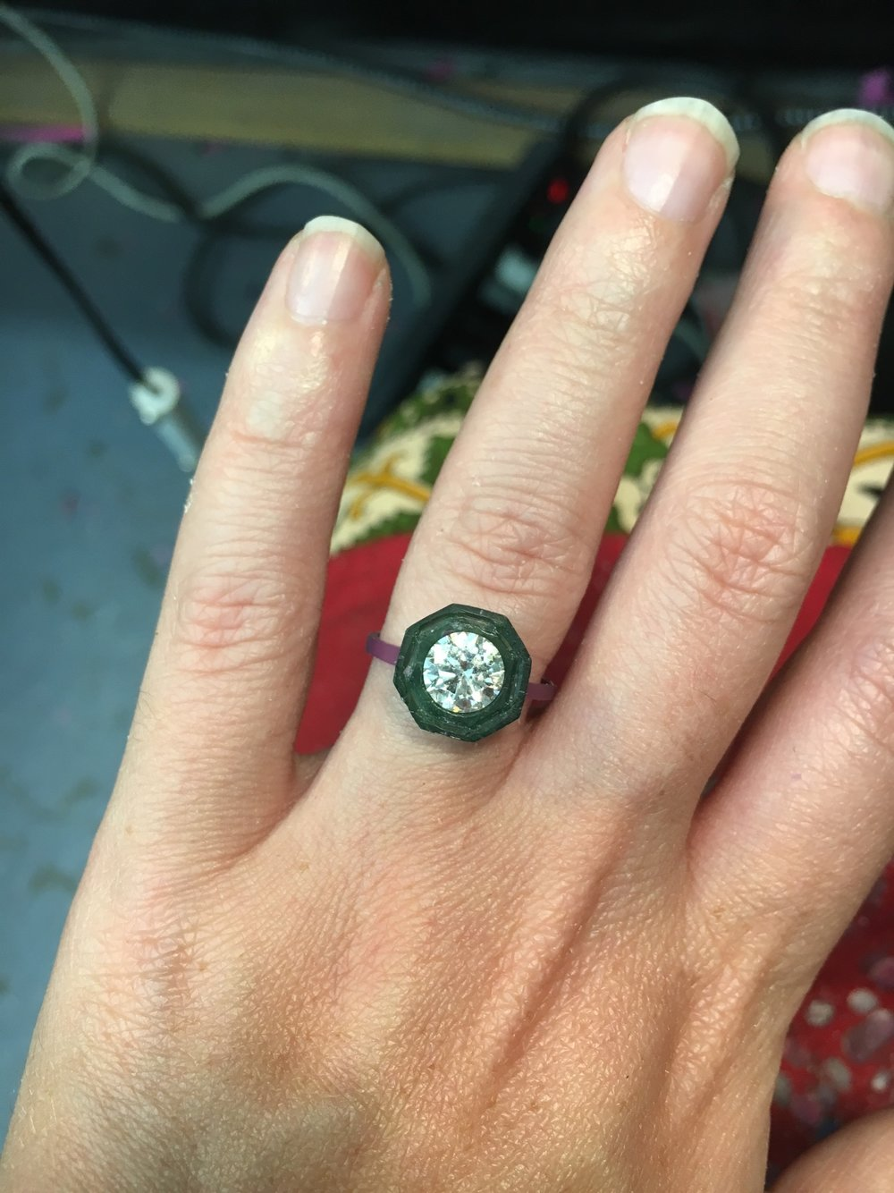 The band is attached to the setting using heat to mend the waxes together. The diamond is just resting on the setting, just in the photo for emphasis!