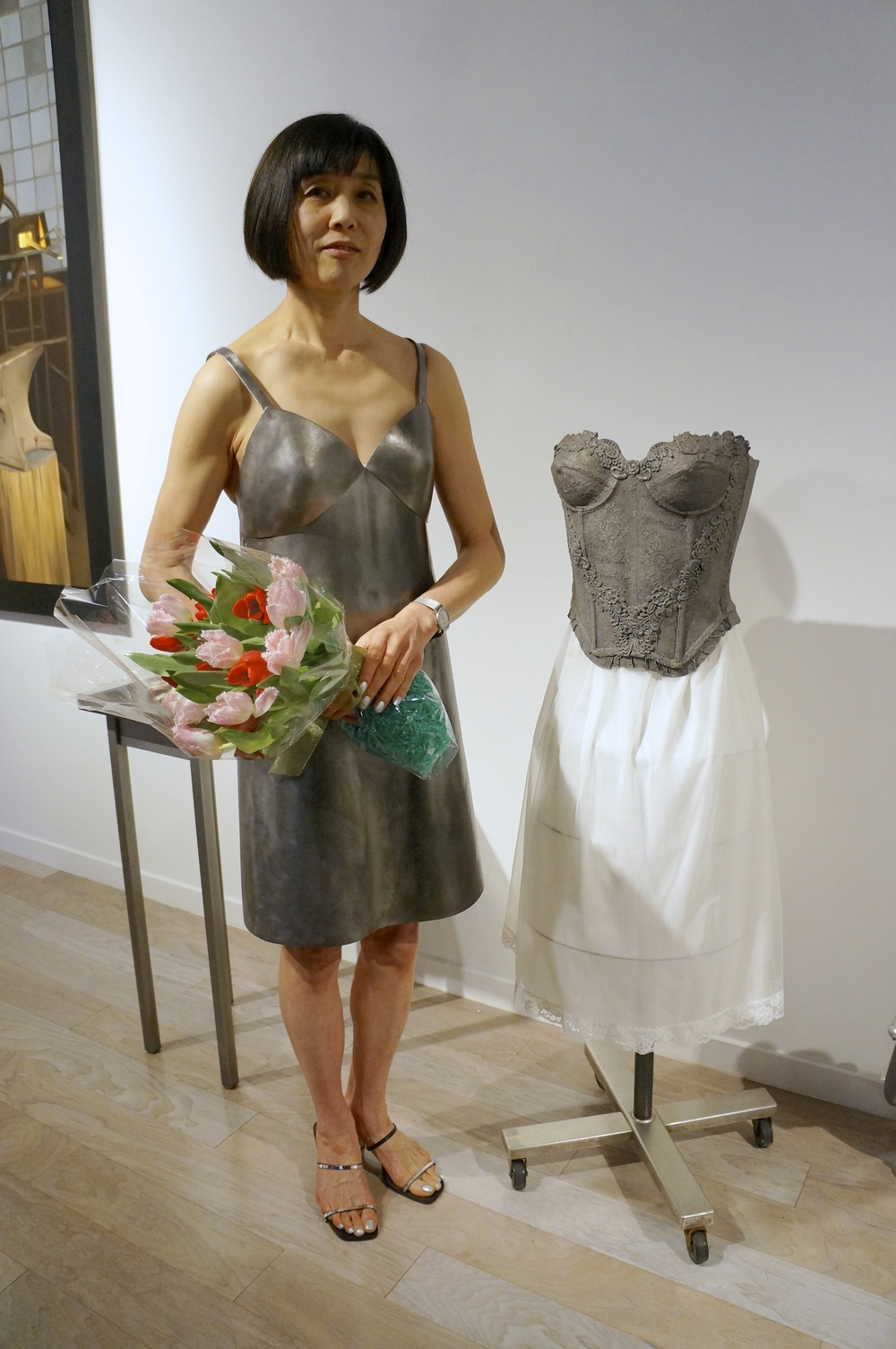 Mayumi Amada wearing her hammered steel dress, standing next to her piece,  Shackles of Convention,  a cast iron and silk corset and skirt.