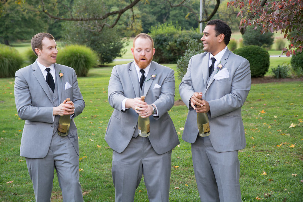 Whitehall Estate and Winery Wedding groomsmen popping champagne Photo