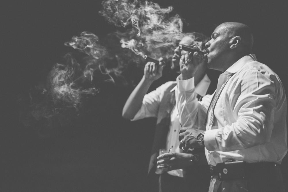 strong manor groom smoking cigar photo