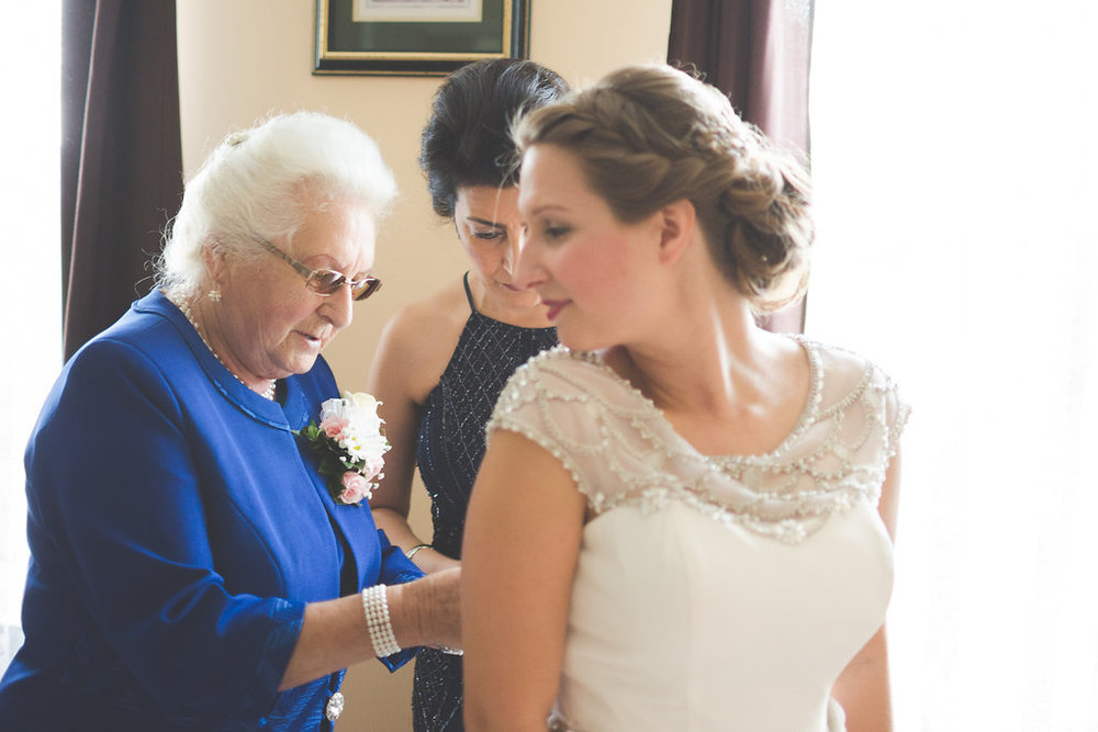 grandmother and bride putting on dress