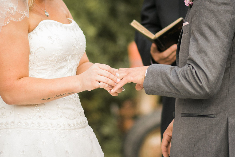 country bride and groom exchange of rings photo