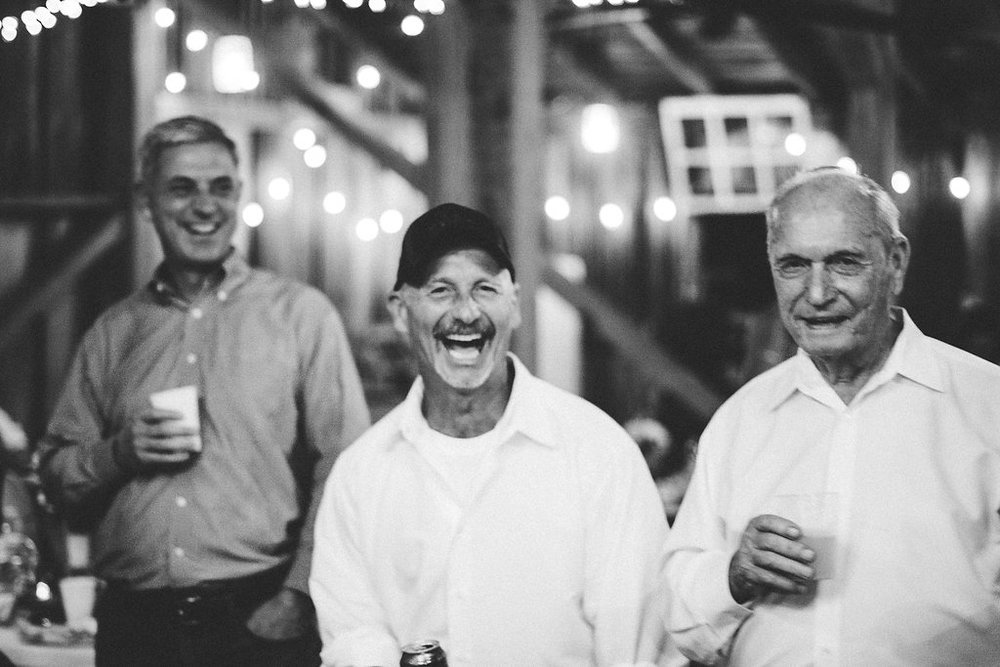 father and grandfather having fun at wedding reception photo