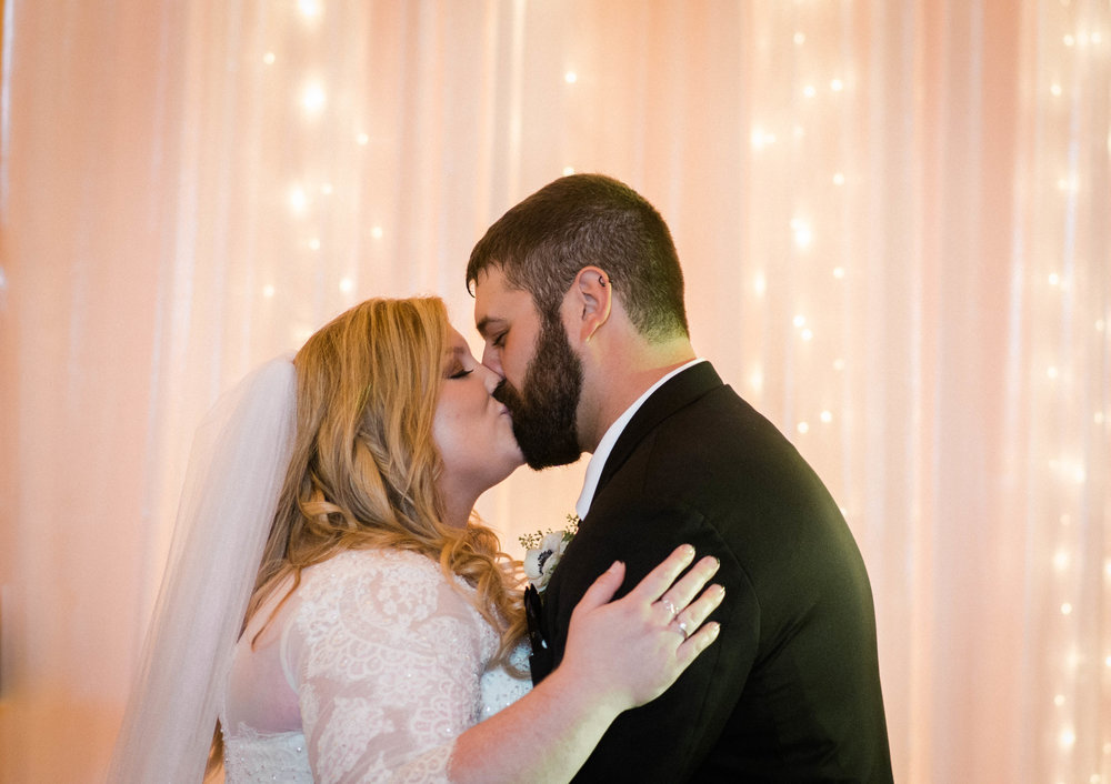 bride and groom first kiss barn ceremony photo