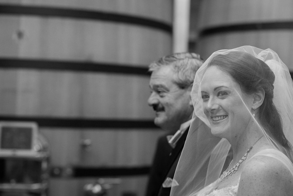 father walking bride down aisle at stone tower winery tank room photo