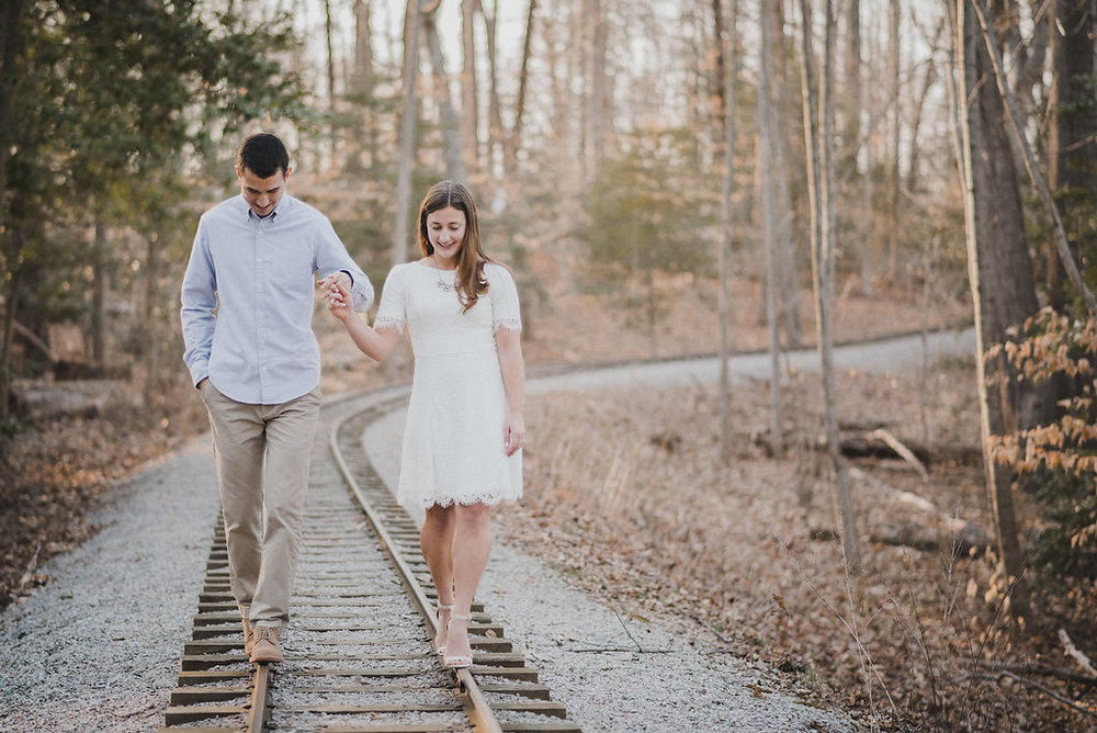 Couple walking on train track holding hands