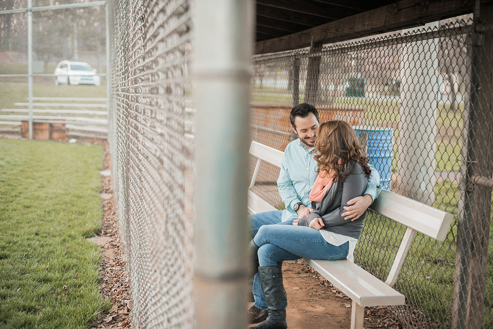 Couple sitting on bench on baseball field