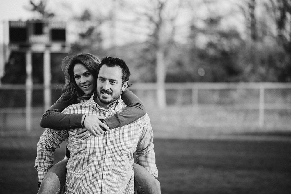 man carrying woman on baseball field