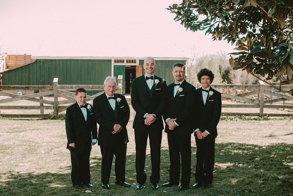 Men in tuxedos in front of barn