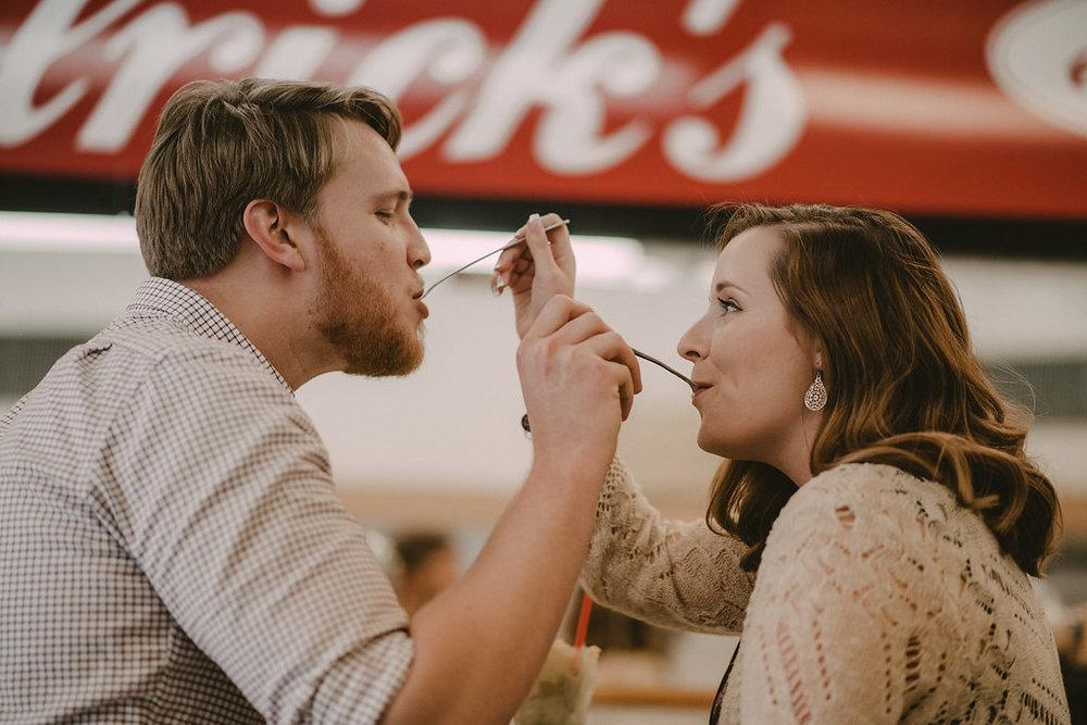 Engagement couple feeding one another ice cream photo