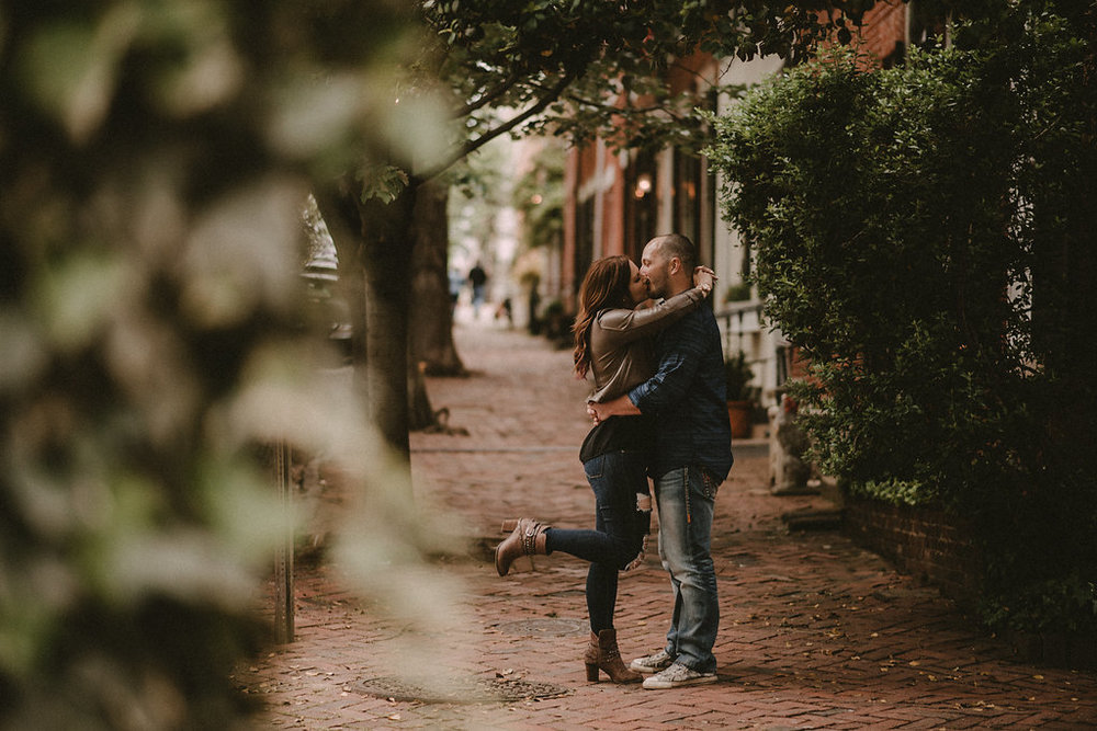 Couple kissing on brick sidewalk
