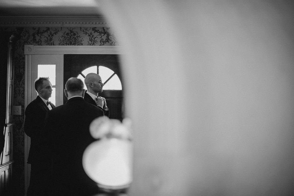 Men getting ready for wedding by door