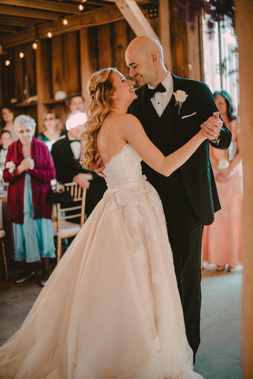 Bride and groom dancing in barn