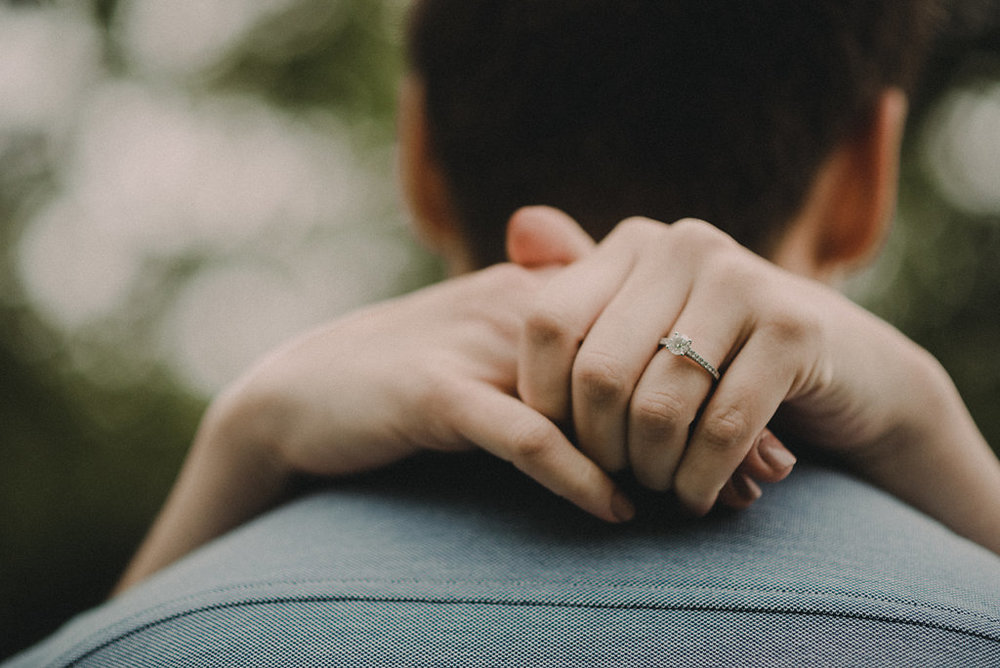 Hands around man's shoulders with engagement ring