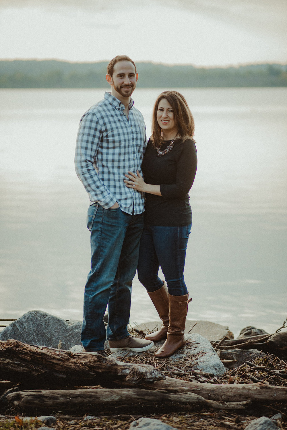Couple posing on rock near river