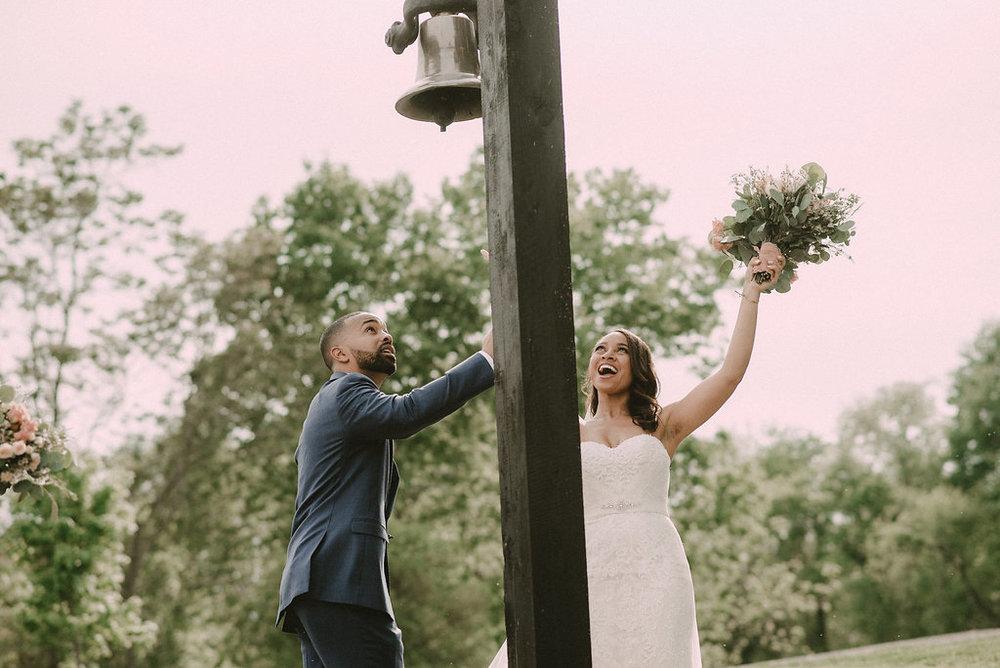 Bride and groom ringing wedding bell at ceremony photo