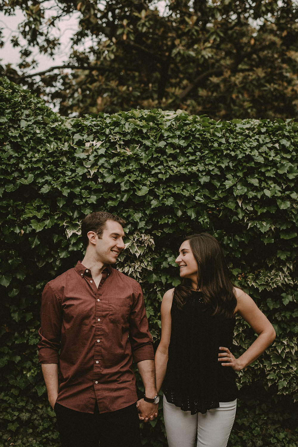 Couple standing in front of ivy wall