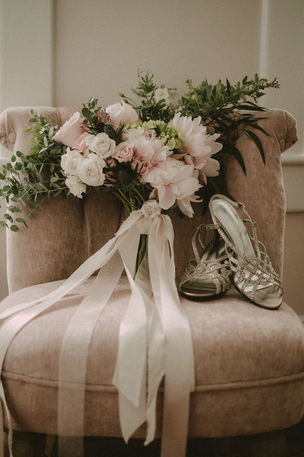 Bouquet and wedding shoes sitting on chair