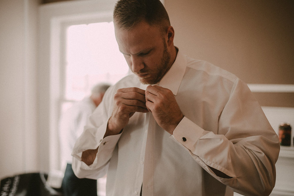 Groom putting on tie before wedding