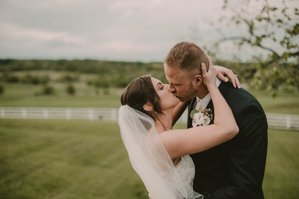 Bride and groom kissing on lawn