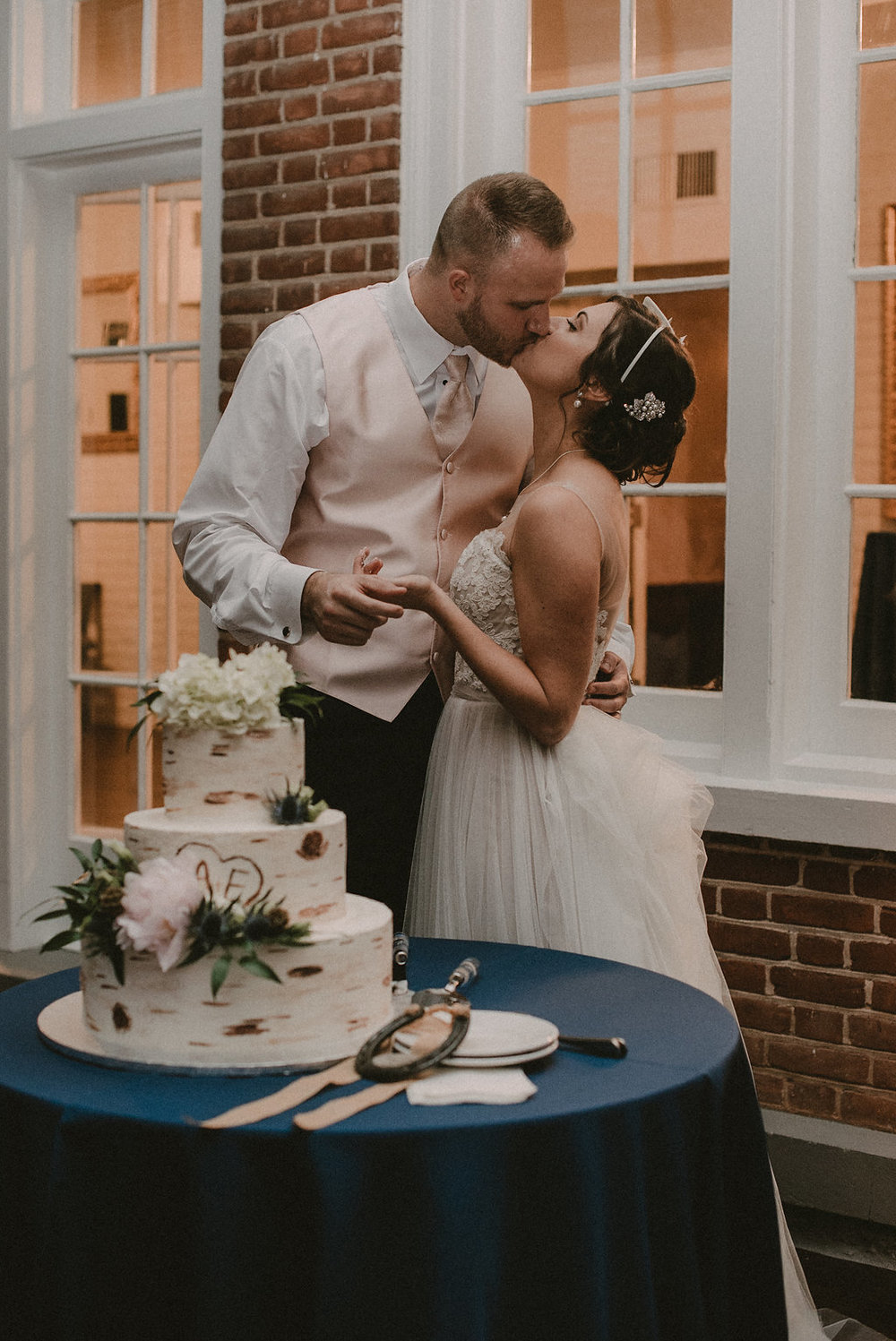 Bride and groom kissing at cake