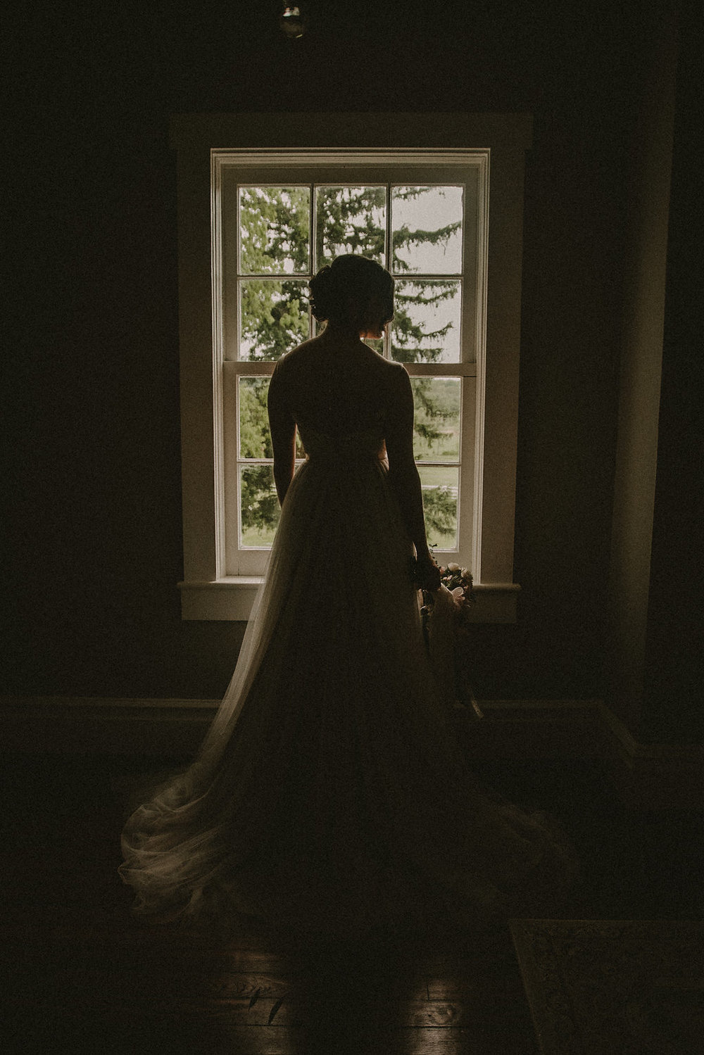 Bride looking out window at wedding ceremony