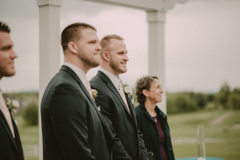 groom seeing bride for first time at ceremony photo