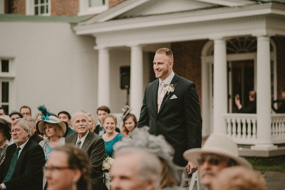 groom walking down ceremony aisle photo