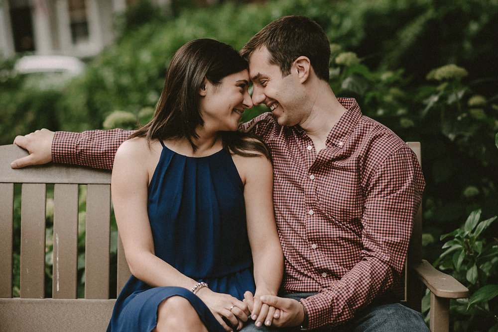 Couple sitting on park bench engagement photo