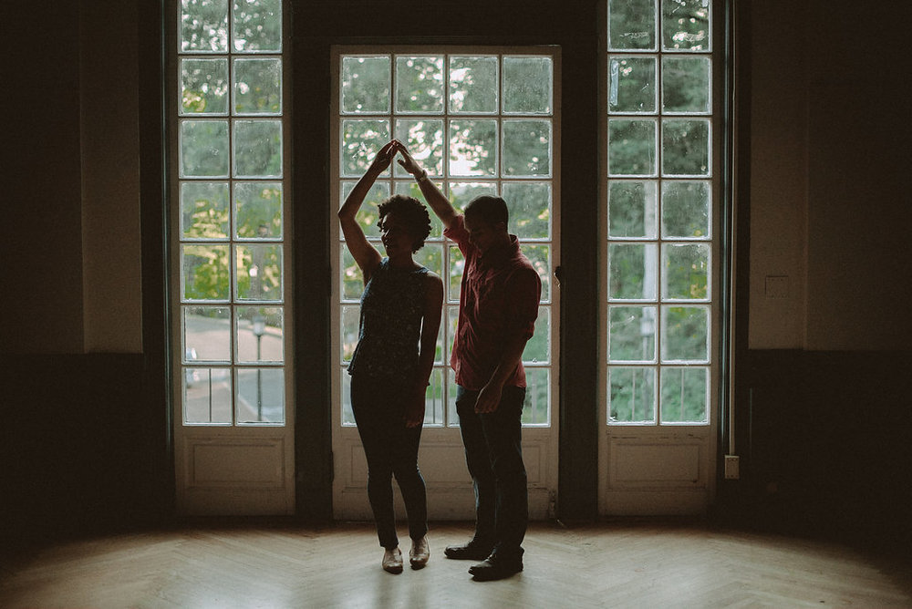 Couple dancing in front of window