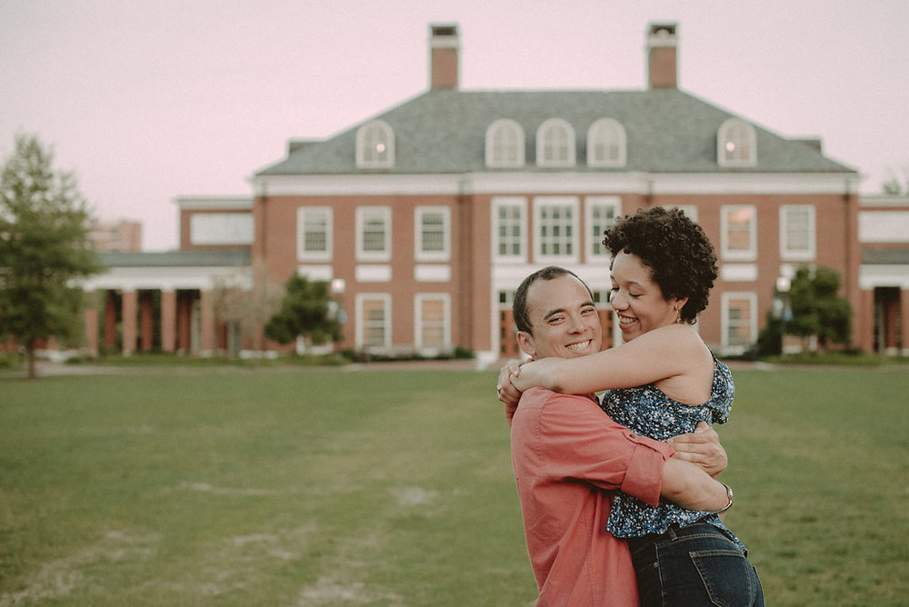 Couple hugging in front of mansion